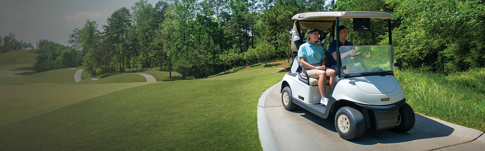 Man and woman riding in an E-Z-GO golf cart on a green golf course.