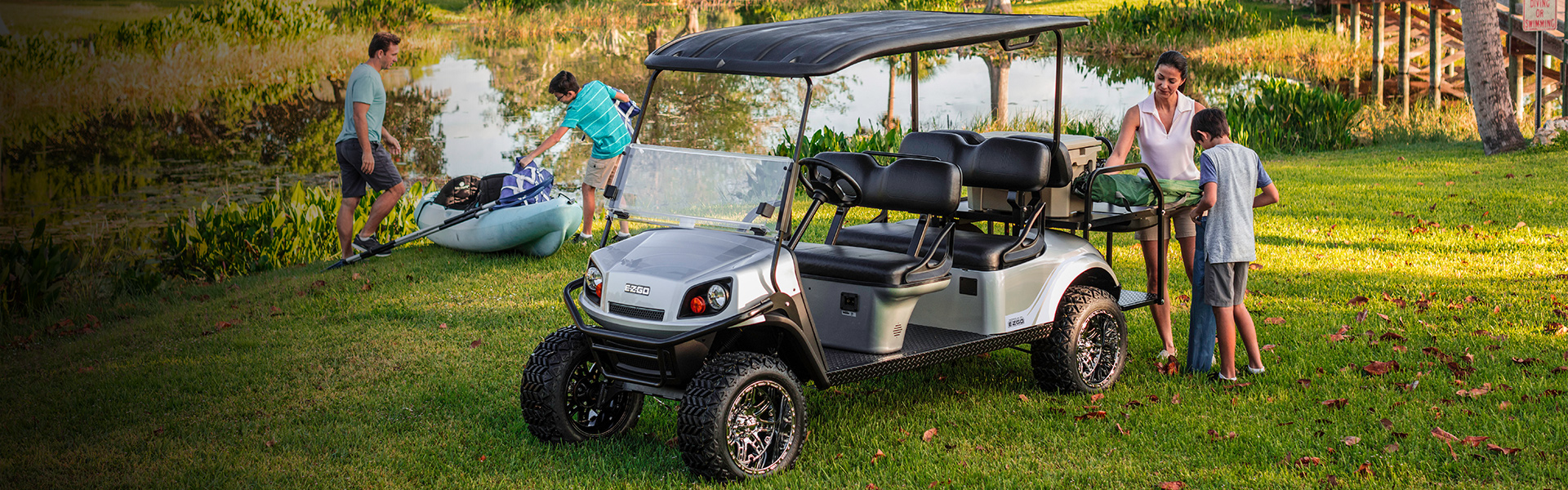 E-Z-GO - A family prepares for a day outdoors along the water after arriving on their E-Z-GO golf cart.